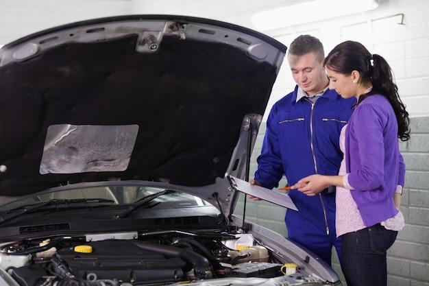 Механик стоит с буфером обмена рядом с клиентом