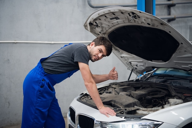 A mechanic stands by the open hood of a car and shows a thumb