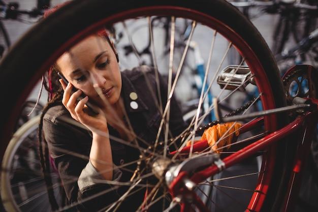 Meccanico parlare al telefono cellulare mentre la riparazione di biciclette