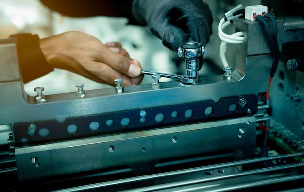工場で産業機械を修正するメカニック技術者の手。プロの技術者サービスとメンテナンス包装機械設備。労働者はレンチ保守産業機械を使用します。