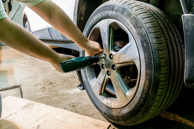 The mechanic unscrews the nuts on the wheel. man exchanging tire. tire service. tire fitting.