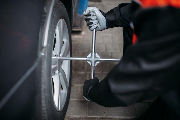 Механик откручивает колесо в шиномонтаже