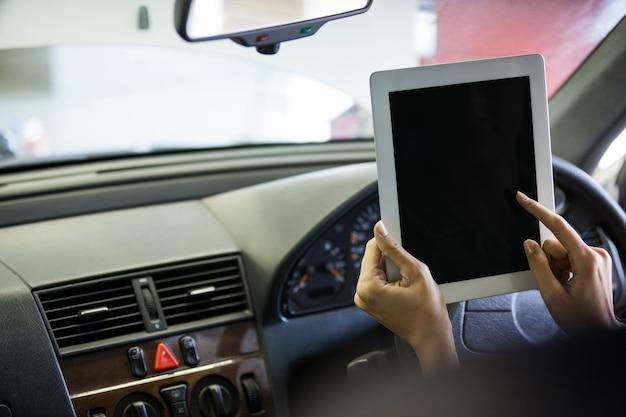 Meccanico con tavoletta digitale in auto
