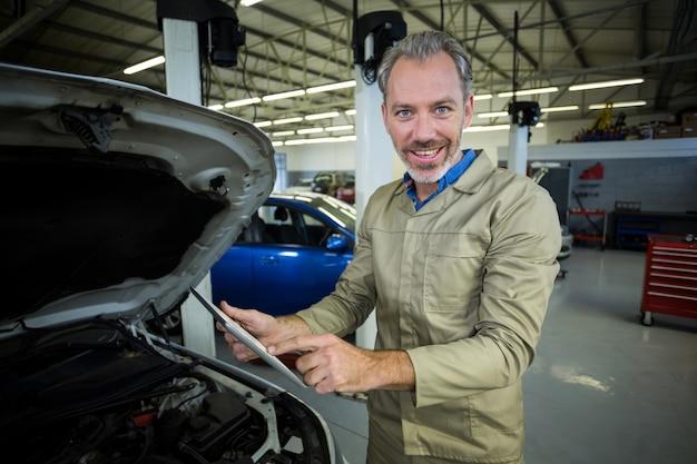Meccanico con tavoletta digitale, mentre la manutenzione di un motore di un'auto