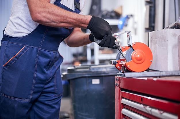 Mechanic using grinding machine at auto repair shop