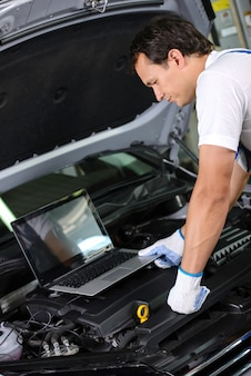 Mechanic using a laptop computer to check a car engine.