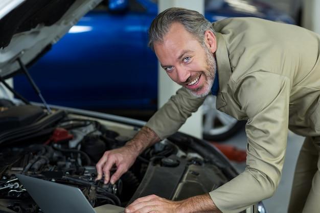 Механик, используя ноутбук во время обслуживания двигателя автомобиля