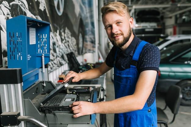 Механик, использующий ноутбук в гараже