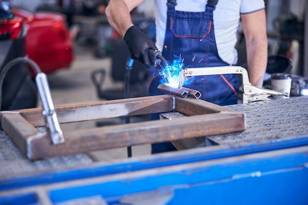 Mechanic using welding torch in auto repair shop