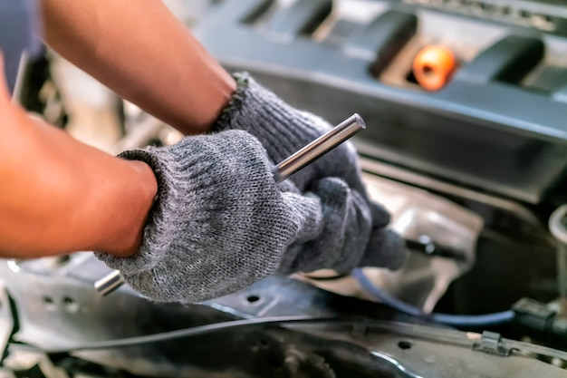 Mechanic using wrench and a screwdriver to work