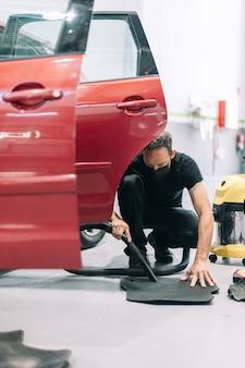 整備士がワークショップで車を掃除機で掃除する