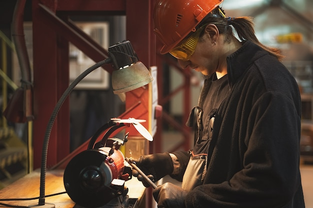 A mechanic wearing gloves glasses and a helmet processes a metal part on a grinding machine