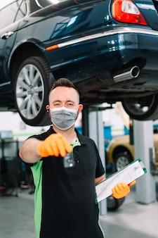 Mechanic wearing surgical mas giving you the car keys