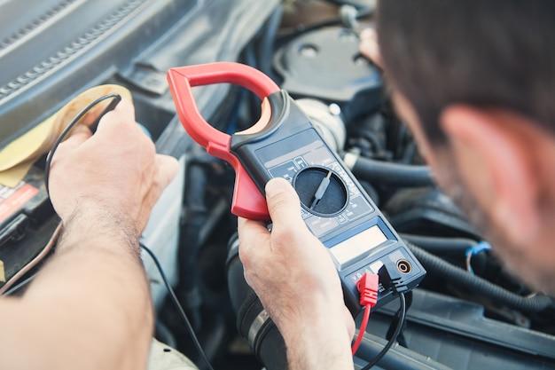 Механик с мультиметром тестирует автомобильный двигатель. автосервис