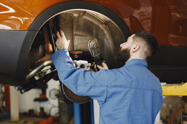 Механик с инструментом. колесо в руках механика. синяя рабочая одежда.
