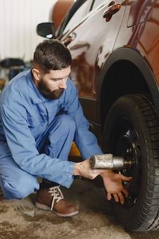 도구가있는 정비공. 정비사의 손에 바퀴. 파란색 작업복.