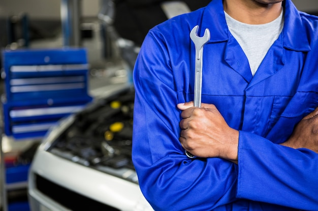Mechanic with arms crossed holding spanner