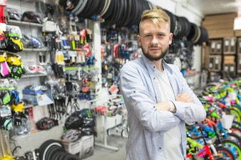 Mechanic with folded arms standing in bicycle workshop