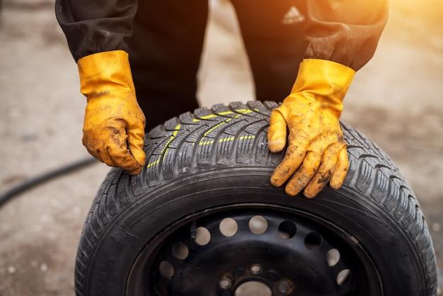Механик в оранжевых перчатках использует мел, чтобы пометить шины, опираясь на одну в своей мастерской.