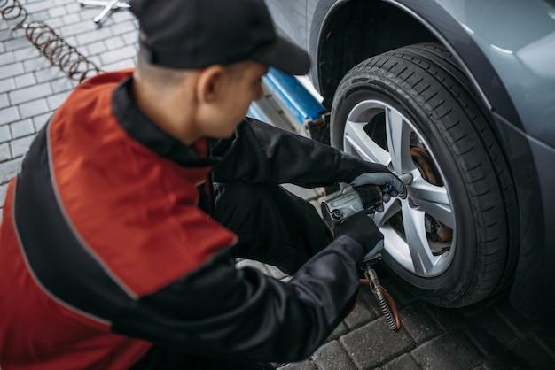 Механик пневматическим ключом откручивает колесо в шиномонтаже. человек ремонтирует автомобильную шину в гараже, автомобильный осмотр в мастерской