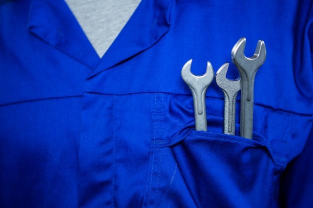 Механик с гаечными ключами в карманах