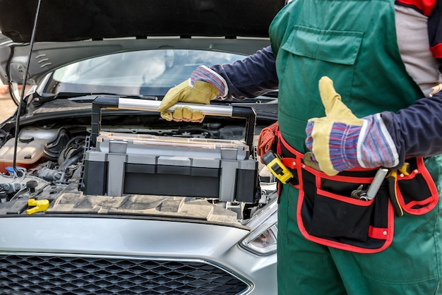 Mechanic with tool box and car with opened hood showing visit card