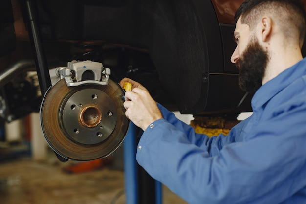 Mechanic with a tool. wheel in hands of a mechanic. blue work clothes.