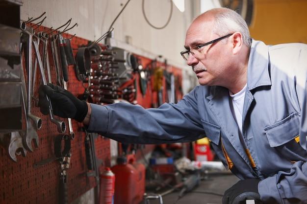 Механик с инструментами в мастерской