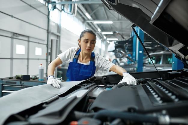 Mechanic woman checks engine in mechanical workshop