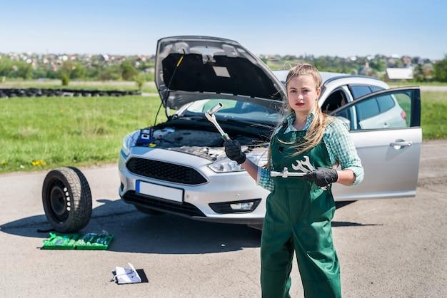 도구와 자동차의 배경에 서있는 정비공 여자