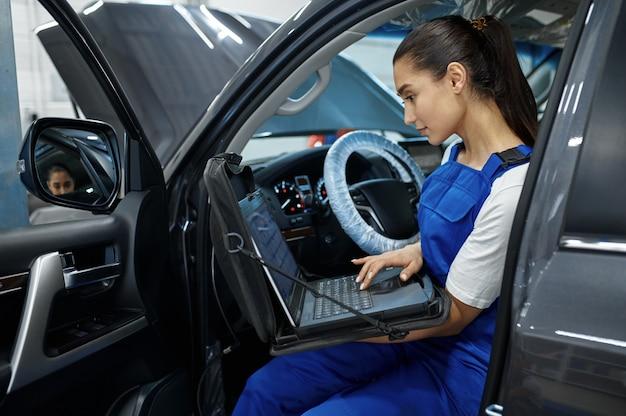Механик женщина с ноутбуком делает диагностику двигателя в механической мастерской, профессиональный осмотр