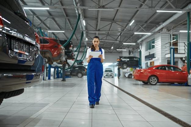Механик женщина с ноутбуком в механической мастерской, профессиональная диагностика