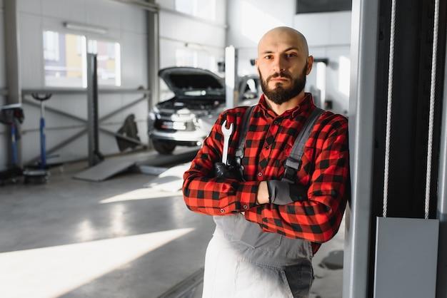 Механик рабочий и удерживающий ключ сервисного заказа для обслуживания автомобиля в ремонтной мастерской