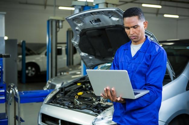 Meccanico che lavora sul computer portatile