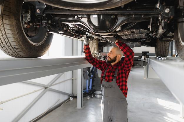 Механик, работающий под автомобилем в ремонтном гараже