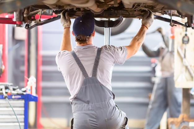 Механик работает с машиной в механической мастерской