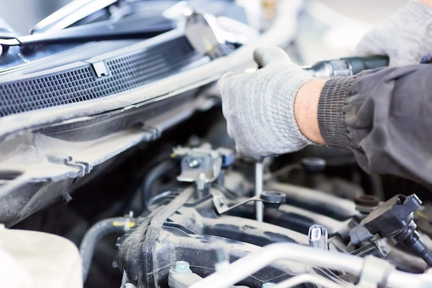 Mechanic working with a car in mechanical workshop