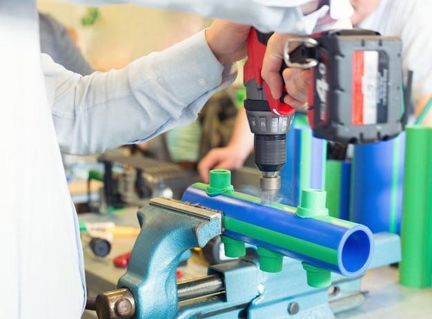 Механик, работающий с трубами в мастерской