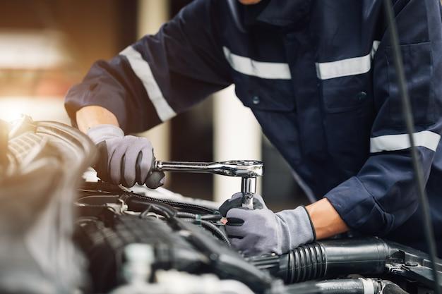 Механик работает над двигателем автомобиля в гараже. услуги по ремонту. концепция автосервиса и автосервиса.