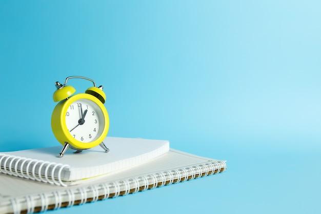 기계식 알람 시계, 파란색 배경에 노트북. 고품질 사진