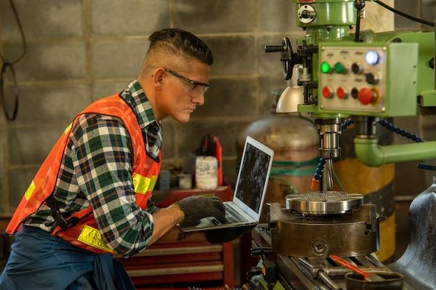 안전 하네스 입고 기계 엔지니어는 공장에서 밀링 머신과 노트북을 사용합니다.