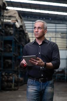 오래된 자동차 부품 대형 창고에서 일하는 동안 노트북 컴퓨터에서 오래된 자동차 부품 재고를 검사하는 기계 남자 소유자 중소기업
