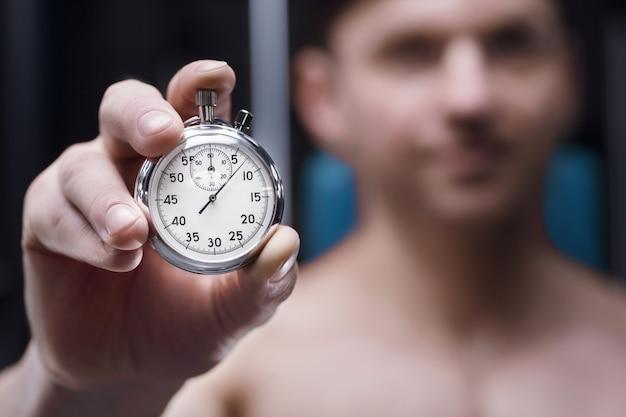 手に機械式ストップウォッチ。時計の文字盤を持つ男性アスリート。フィットネスとスポーツのコンセプト