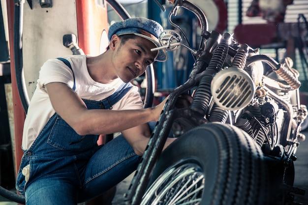 Техник-механик ремонтирует мотоцикл в мастерской