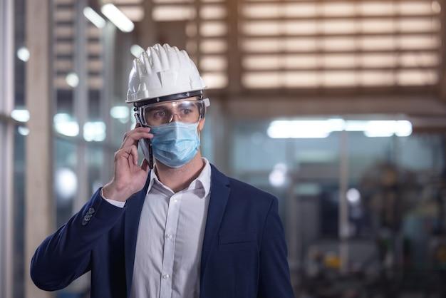 Механик с маской разговаривает по телефону на заводе