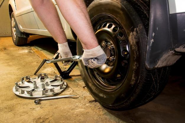 정비사는 차고에서 자동차 바퀴를 변경합니다. 남자 교환 타이어입니다. 타이어 서비스. 타이어 피팅.