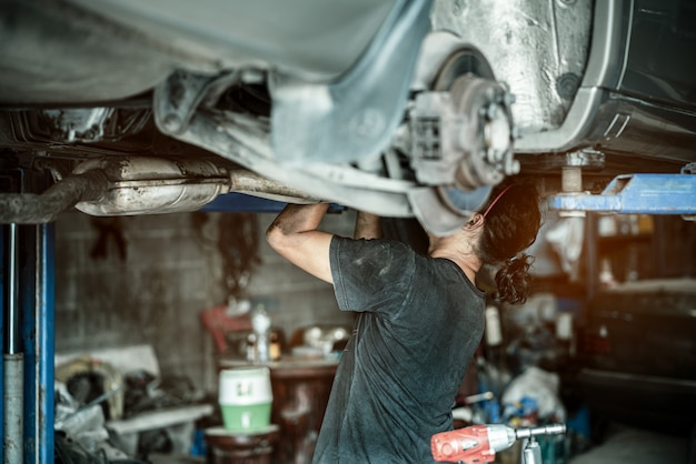 Mechanician repairing car in garage under the car.