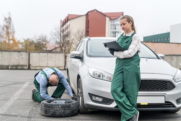 Mechanics changing wheel of a car at service
