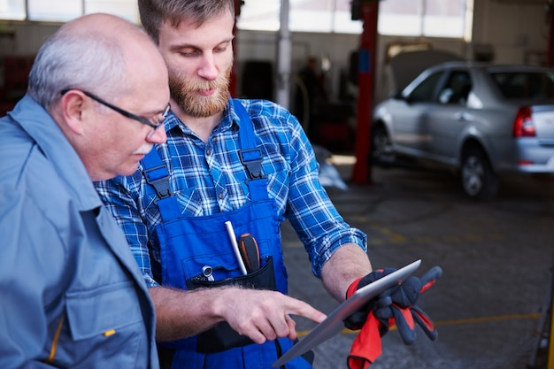 Механики, проверяющие планировку в мастерской