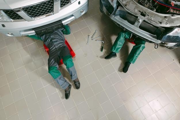 Механики в униформе, лежа и работая под машиной в гараже